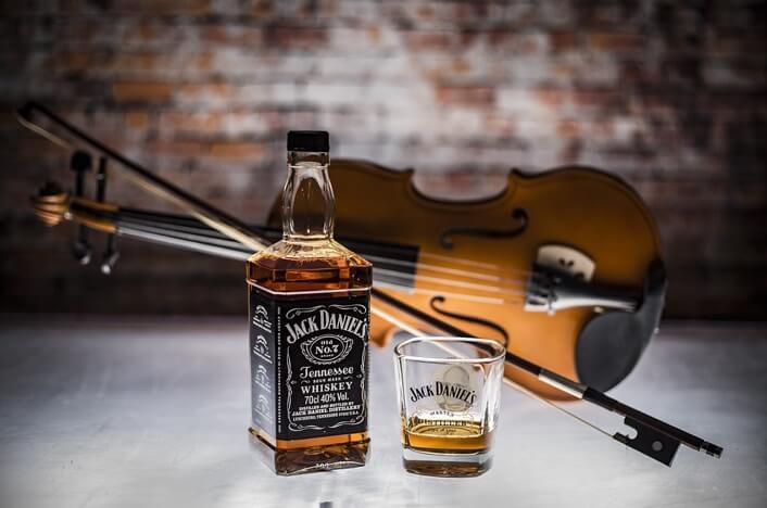 botella de whisky con violin detras